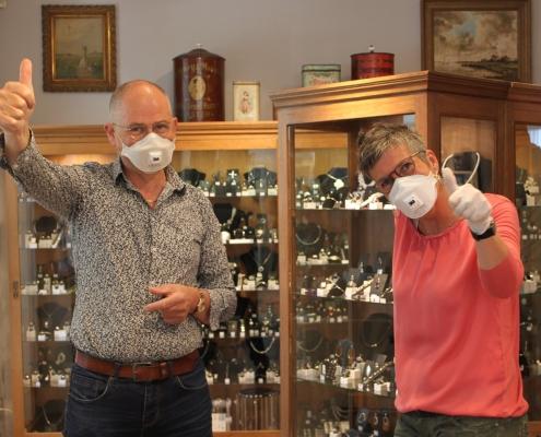Geschäftsinhaber mit Atemschutzmaske zeigen mit dem Daumen hoch