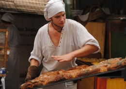 Ein Bäcker zieht ein Backblech mit frischem Brot aus dem Ofen