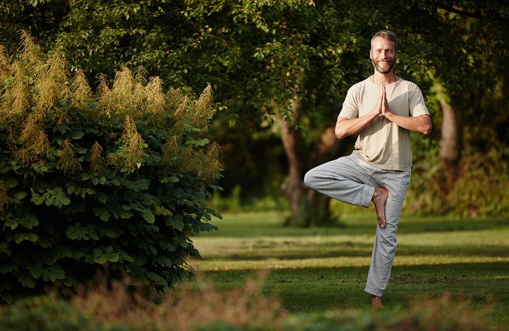 Lächelnder Mann steht im Park auf einem Bein in einer Yogastellung