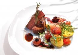 Culinaria-Menü auf Teller, Rindfleich und Kartoffeln, mit Rucola garniert