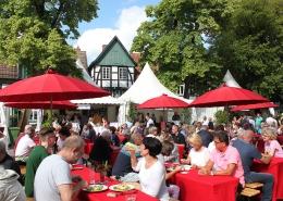 Menschen tafeln während der Culinaria auf dem Kirchplatz vor dem kleinen Haus