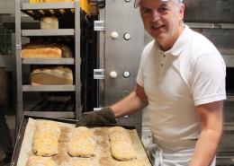 Familienbäckerei Titgemeyer, Bäcker präsentiert Backblech mit Ciabatta