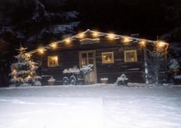 Aussenansicht der Enzianhütte nachts im Winter bei Schnee