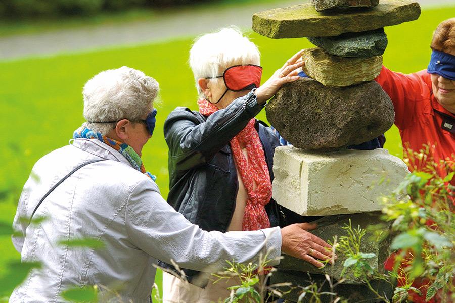 Drei Frauen mit verbundenen Augen ertasten diverse Steine auf dem Weg der Sinne