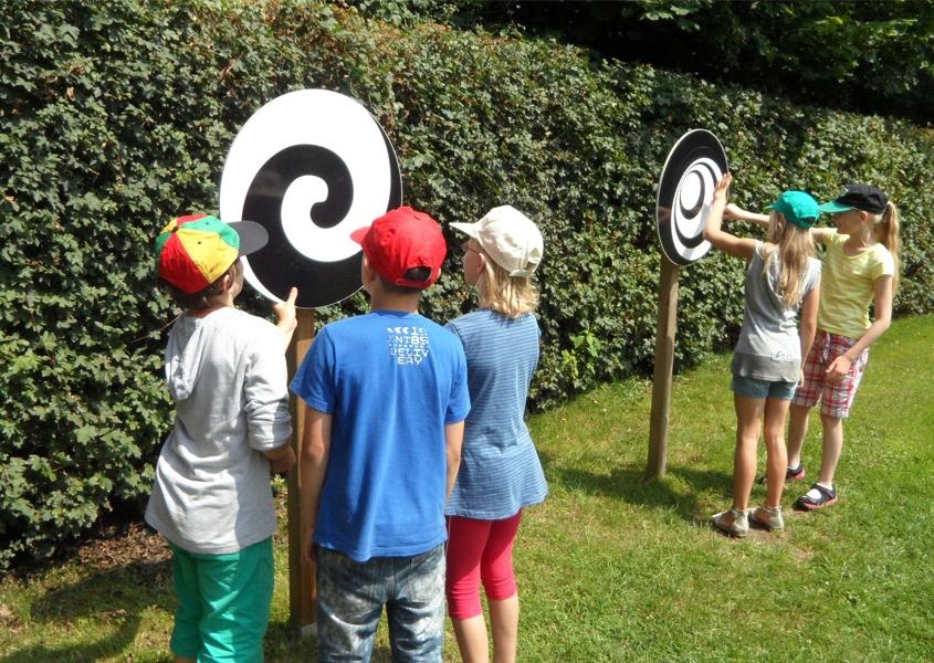 Kinder drehen im Familienpark an den Rädern, die optische Täuschungen erzeugen