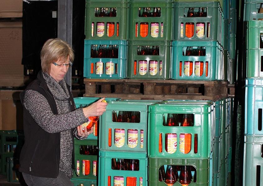 Süßmostkelterei Lammersiek, Frau Lammersiek begutachtet Flasche mit Direktsaft