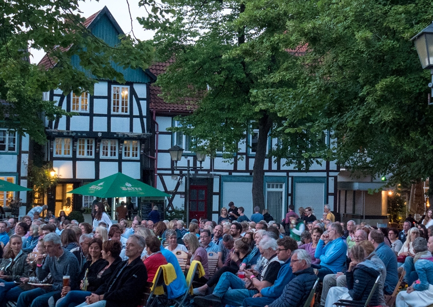 Blick auf das kleine Haus während einer Veranstaltung auf dem Kirchplatz, im Vordergrund Publikum