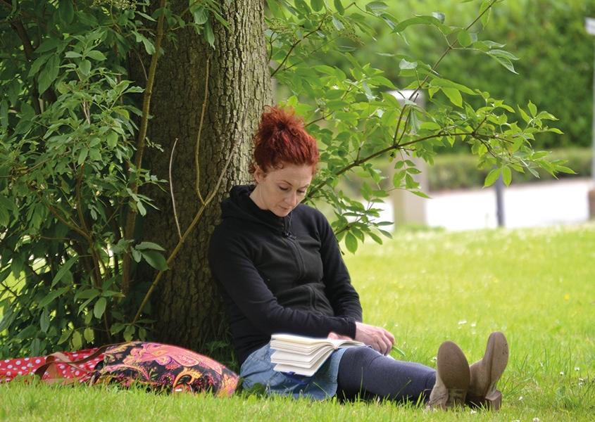 Eine Frau sitzt angelehnt an einen Baum auf dem Rasen und liest ein Buch