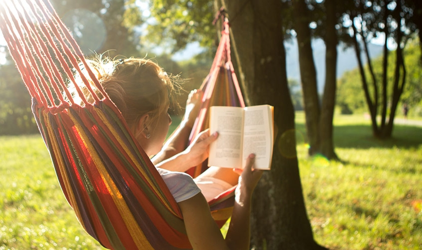 Eine Frau liest ein Buch in der Hängematte an einem Sommertag