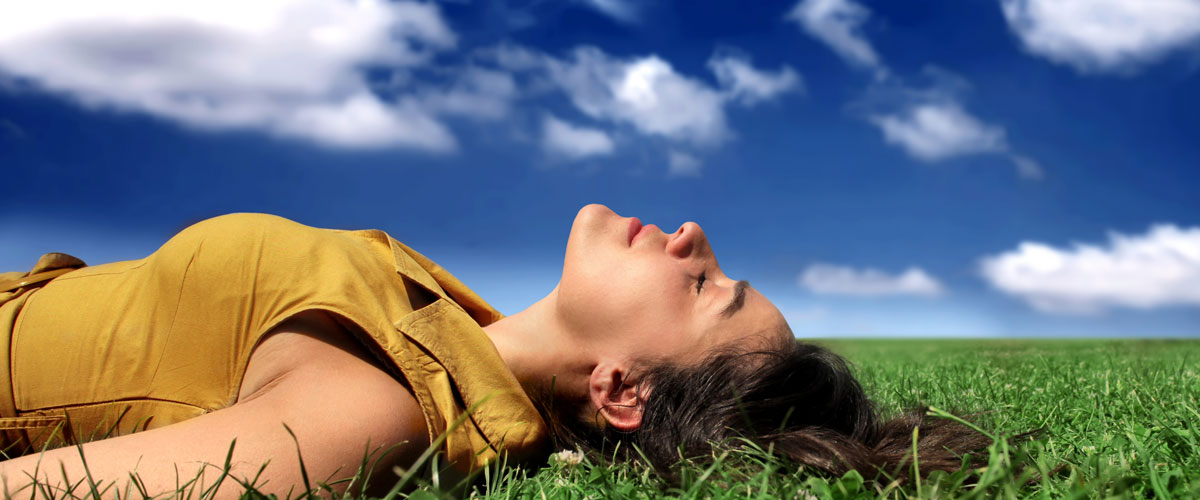 Eine Frau liegt entspannt auf dem Rücken im grünem Rasen im Sommer