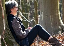 Eine Frau sitzt mit dem Rücken an einen Baum gelehnt