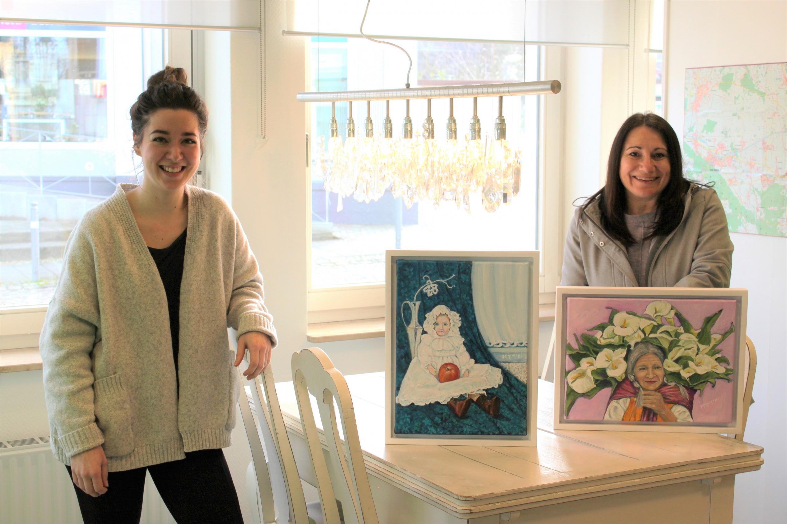 Zwei gemalte Kunstwerke auf weißem Tisch, daneben stehen zwei Frauen