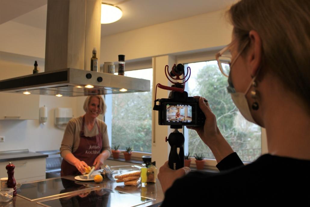 Frau hält Kamera und filmt andere Frau beim Kochen
