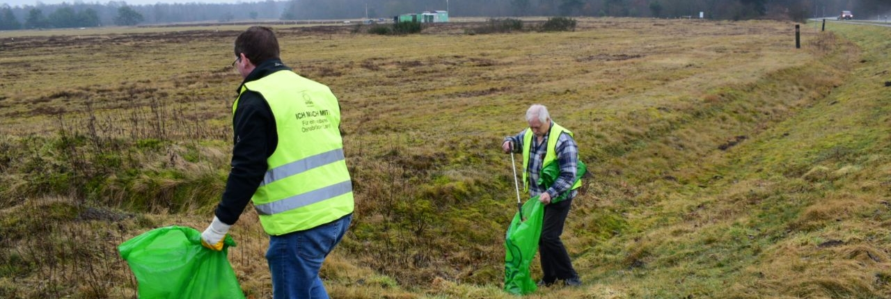 Zwei Männer auf dem Feld mit Mülltuten in der Hand
