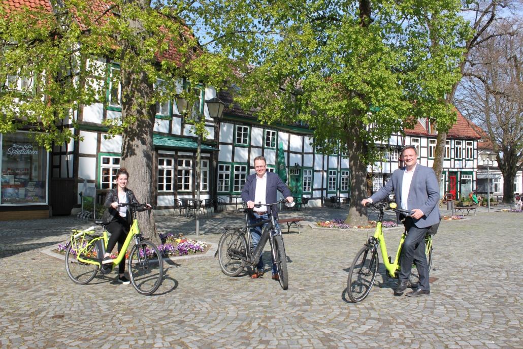 Eine Frau und zwei Männer stehend mit Fahrrädern