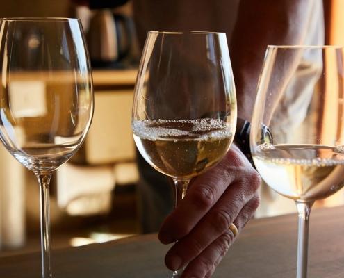 Drei Weingläser, eines von Hand umschlossen